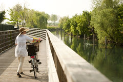Woman with bike by river. Woman with bike walking by river Royalty Free Stock Photos