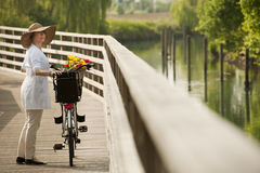 Woman with bike by river. Woman with bike walking by river Royalty Free Stock Images