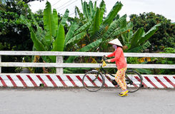 A woman with bike on rural road in Sadek, southern Vietnam Stock Photos