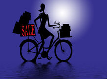 Woman on bike after shopping. Woman with Sale sign on bike loaded with presents Royalty Free Stock Photos