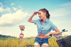 Woman with bike standing on road and looking to somewhere Stock Images