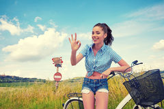 Woman with bike standing on road and looking to somewhere Stock Photo