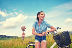Woman with bike standing on road and looking to somewhere. Young woman on bike standing on road and looking to somewhere Royalty Free Stock Photography