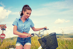 Woman with bike standing on road and looking to somewhere. Young woman on bike standing on road and looking to somewhere Stock Photos
