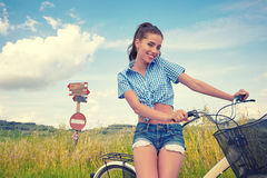 Woman with bike standing on road and looking to somewhere Royalty Free Stock Images