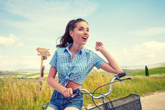 Woman with bike standing on road and looking to somewhere Stock Photos