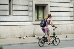 Woman on bike in a street. BRUSSELS, BELGIUM - JULY 4, 2015: A woman on a folding bike, stroll down one of the streets of the city Royalty Free Stock Image
