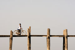 Woman with bike on U Bein bridge in Amarapura, Myanmar (Burma) Royalty Free Stock Images