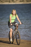 Woman on bike by water Royalty Free Stock Photo