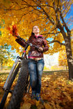 Woman with bike on a yellow leafs background Stock Image