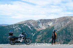 Woman biker and adveture motorcycle top mountain road. Travel, vacation in Europe, motorcyclist way, tourism, Transalpina, Romania royalty free stock image