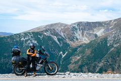 Woman biker and adveture motorcycle top mountain road. Travel, vacation in Europe, motorcyclist way, tourism, Transalpina, Romania stock photo