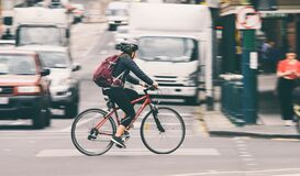 Woman biker commuting on bicycle in busy city street
