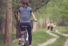 Woman biker cycling in park from behind royalty free stock photos