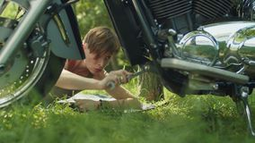 Woman biker fixing motorcycle part with wrench stock footage