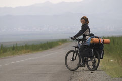 Woman biker on a road. Woman biker going on a road, Mongolia. Selected focus Royalty Free Stock Photos