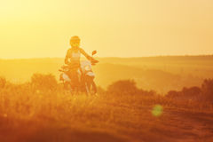 Woman biker in sunset, female motorcycle. Royalty Free Stock Photos