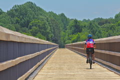 Woman biking a bridge on a Virginia Trail Stock Photo