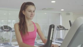 Woman biking in the gym, close up. Fitness woman biking in the gym, doing cardio training, close up stock video footage
