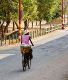 A woman biking on rural road in Bagan, Myanmar Royalty Free Stock Photos