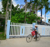 A woman biking on rural road in Hoi an, Vietnam Royalty Free Stock Image