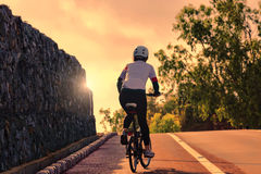 Woman biking uphill road Stock Image