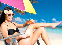 Woman in bikini applying sun block cream on body Royalty Free Stock Photo