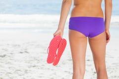 Woman in bikini on beach holding flip flops Royalty Free Stock Photos