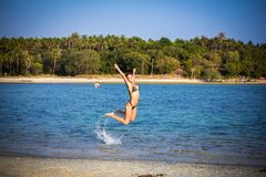 Woman in bikini on the beach jumping under water Royalty Free Stock Image