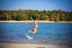 Woman in bikini on the beach jumping under water. Woman in bikini on beach jumping in the water Royalty Free Stock Image