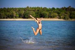 Woman in bikini on the beach jumping under water Stock Photo