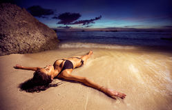 Woman in bikini on the beach at sunset. Beautiful young woman in bikini on the beach at sunset Royalty Free Stock Images
