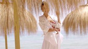 Woman in bikini and beach top under umbrella stock video