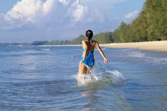 Woman with bikini blue sexy jump on wave at beach. Ban Krut Beach, in Prachap Kirikhun Province Thailand is famous for travel stock photography