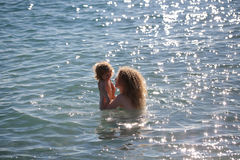 Woman in bikini with child. Young mother in bikini standing swimming and playing with male child boy in sea or ocean water sunny day outdoor on natural Stock Photos