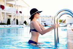 Woman in bikini coming out from swimming pool Stock Photo