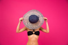 Woman in bikini covering her face with hat Stock Photography
