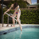 Woman in bikini dipping toe in pool. A beautiful young brunette woman dipping her toe into the pool to see how cold the water is Royalty Free Stock Image