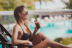 Woman in bikini drinking a cocktail on the terrace Royalty Free Stock Photography