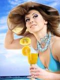 Woman in bikini drinking orange juice. Stock Photos