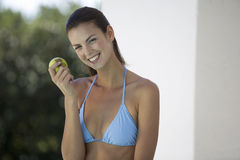 A woman in a bikini eating an apple Royalty Free Stock Image