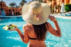 Woman in bikini eating fruits and relaxing in swimming pool. All inclusive. Summer vacation stock photos