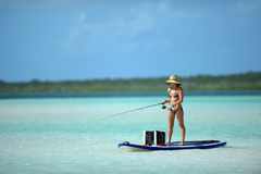 Woman in bikini fishing and paddle boarding Royalty Free Stock Photos