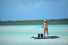 Woman in bikini fishing and paddle boarding Royalty Free Stock Photos
