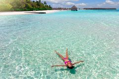 Woman in bikini floats on the turquoise, tropical sea of the Maldives royalty free stock photos