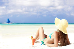 Woman in bikini with fresn watermelon juice on tropical beach. Attractive young woman in blue bikini and straw hat with fresh juice on tropical boracay beach Royalty Free Stock Image