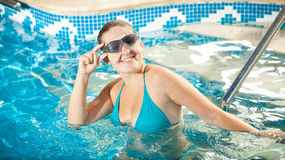 Woman in bikini and goggles smiling at camera at swimming pool Royalty Free Stock Images