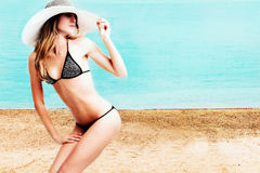 woman in bikini and hat on beach Stock Photo