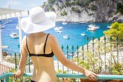 Woman in bikini and hat looking at Marina Piccola beach, Capri, Royalty Free Stock Photography