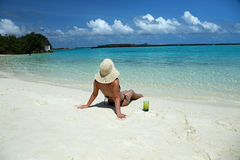 Woman in bikini and hat relaxing on the sea coast of Maldives. Woman wearing bikini and hat relaxing on the sand with drinks on the side. Sunbath on the sea Royalty Free Stock Image